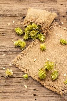 Lúpulo inteiro no saco na mesa antiga de madeira. cervejaria. ingredientes da cerveja. saco de lúpulo em placas vintage