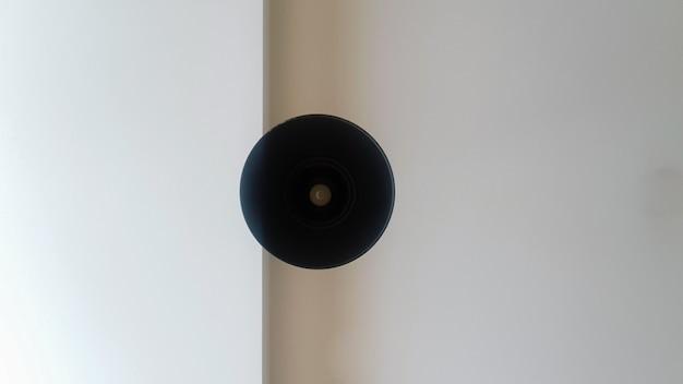 Lustre de teto redondo preto ou lâmpada pendurada em branco do teto. vista inferior de uma lâmpada. decoração arquitetônica no teto, lustre redondo pendurado. minimalismo.