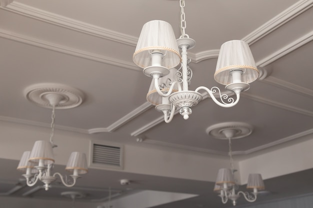 Lustres com três lâmpadas elétricas e abajures pendurados no teto