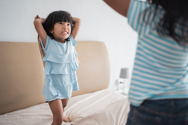 Luta de almofadas de criança na cama
