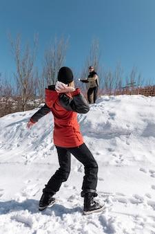 Luta de bola de neve de pessoas em tiro completo