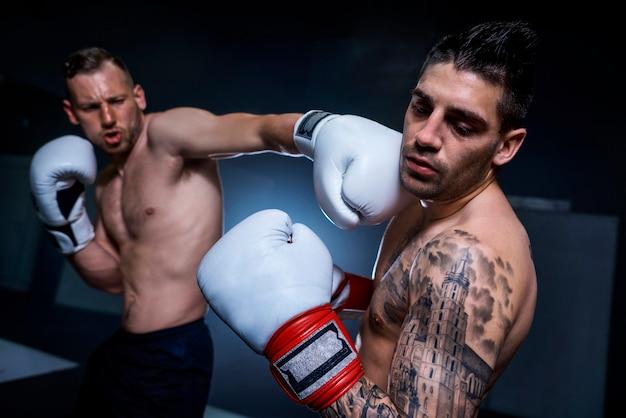 Luta de boxe em ação entre dois atletas masculinos