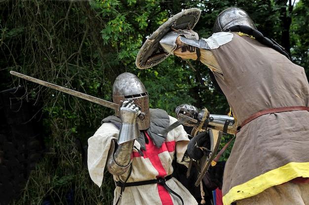Luta de cavaleiros medievais. cavaleiros de armadura. cavaleiros de armadura lutando entre as árvores na floresta