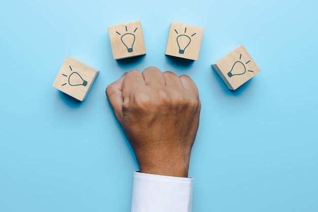 Luta de punho para o sucesso, mão do empresário mostra a luta com a ideia de realização, lâmpada no bloco de madeira em fundo azul suave, inovação e conceito criativo