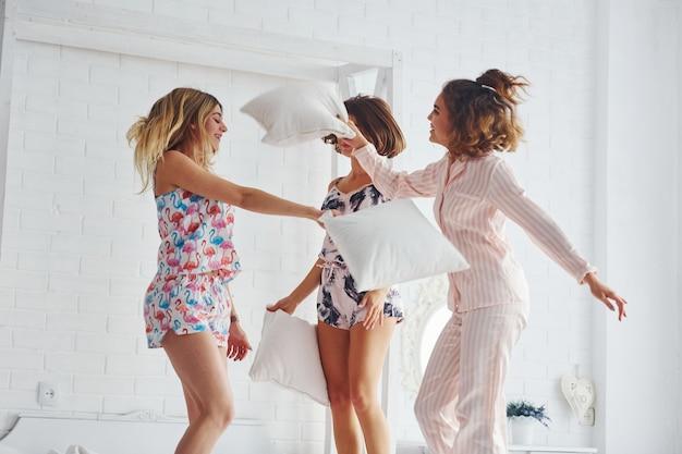 Luta de travesseiro. felizes amigas se divertindo na festa do pijama no quarto.