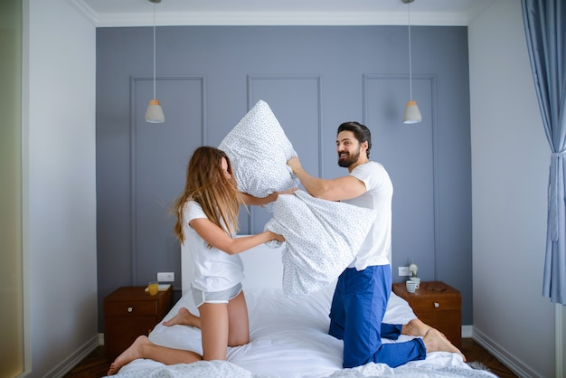 Luta de travesseiro! jovem casal lindo tendo a luta de almofadas em seu quarto. se divertindo e sorrindo.