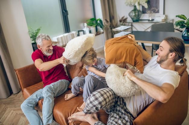 Luta de travesseiro. lindo menino loiro e dois homens brigando de travesseiro e se sentindo felizes