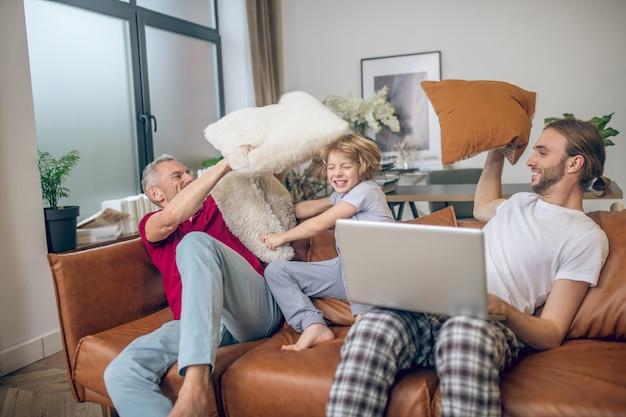 Luta de travesseiro. menino loiro fofo e dois homens brigando de travesseiro