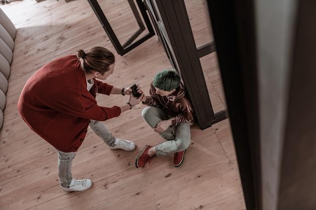 Luta por smartphone. vista superior de casal brigando por causa de smartphone e mensagens pessoais