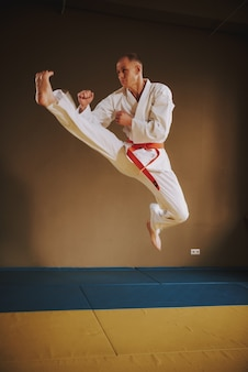 Lutador de artes marciais em branco pulando com chute