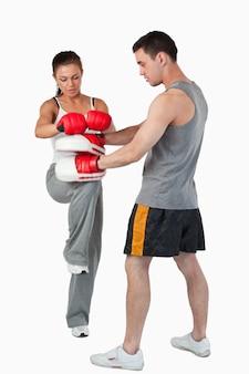 Lutador de artes marciais feminino praticando sua técnica de joelho