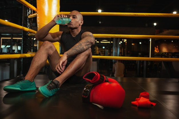 Lutador de boxe masculino africano bonito treinando na academia