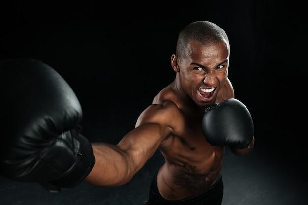 Lutador de caixa de homem afro-americano musculoso praticando chutes