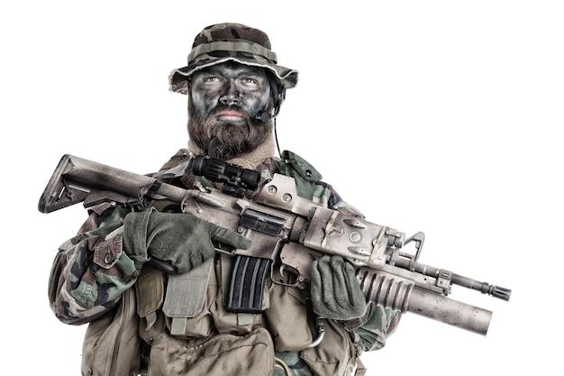 Lutador de comando sério, mercenário da companhia militar com pintura de camuflagem no rosto barbudo, segurando um rifle de assalto com lançador de granadas e mira a laser, tiro em estúdio isolado no fundo branco