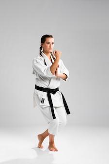 Lutador de garota em posição de combate, vestindo o uniforme branco sobre fundo cinza