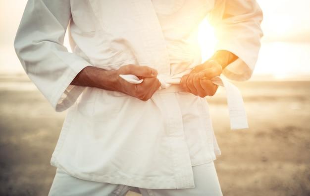 Lutador de karatê, amarrando o cinto do quimono