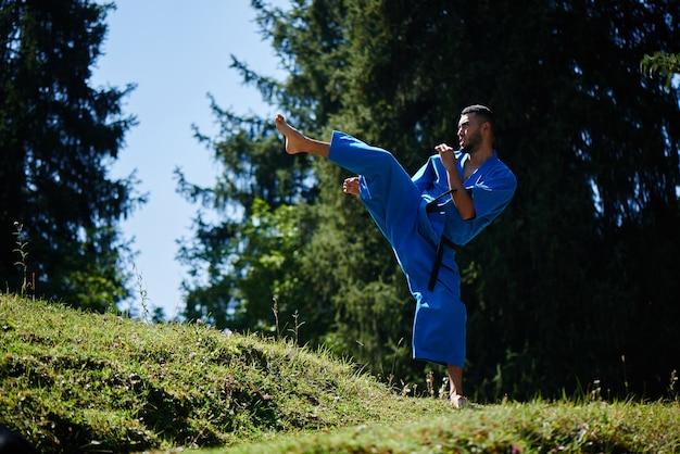 Lutador de karatê do cazaquistão asiático é o combate no quimono azul uniforme em uma paisagem bonita da natureza do verão com espaço da cópia