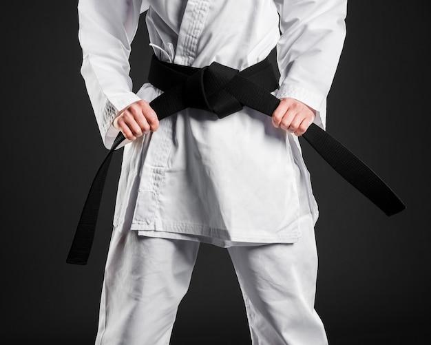 Lutador de karatê orgulhosamente segurando faixa preta