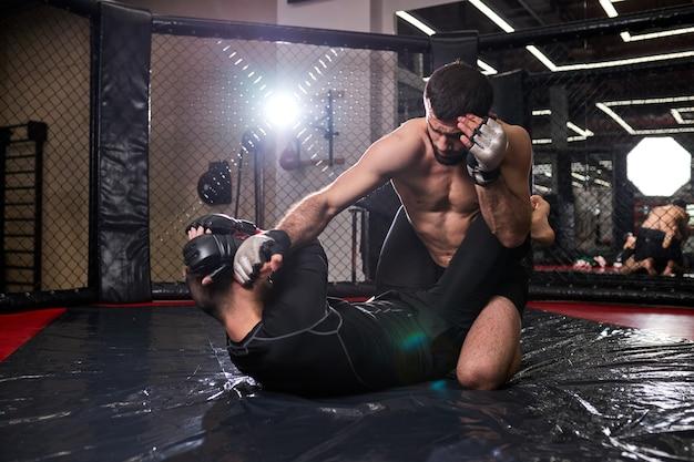 Lutador de mma agressivo socando oponente no chão sobre o tatame da academia, durante luta sem regras. conceito de mma, homem sem camisa sentado no adversário socando