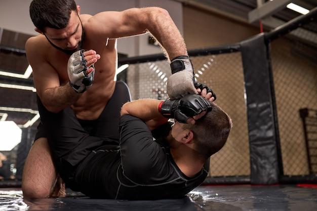 Lutador de mma forte sem camisa em luvas de boxe sentado acima do oponente enquanto desportista deitado no chão resistindo, durante luta sem regras, na academia, treinando