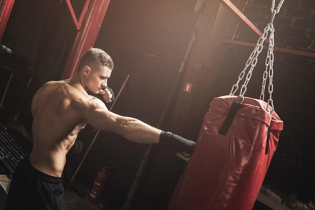 Lutador de mma jovem forte e saco de boxe vermelho