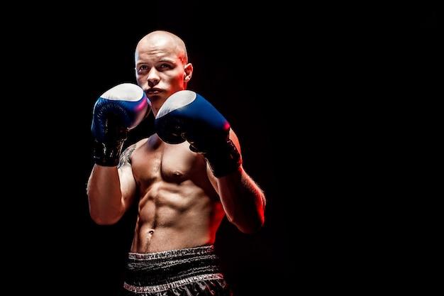 Lutador de muay thai muscular socando na escuridão