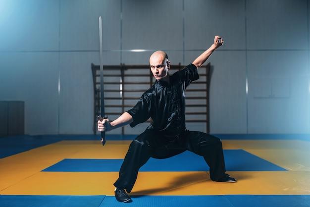 Lutador de wushu com espada em ação, artes marciais. homem de pano preto posa com lâmina