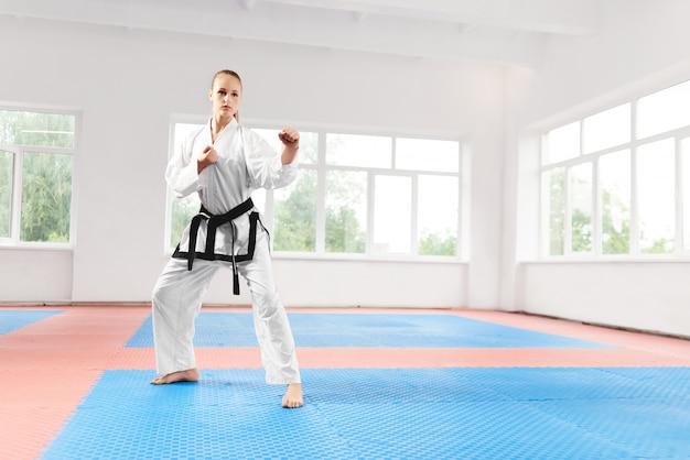Lutador feminino em pé em pose com os punhos cerrados prontos para a batalha.