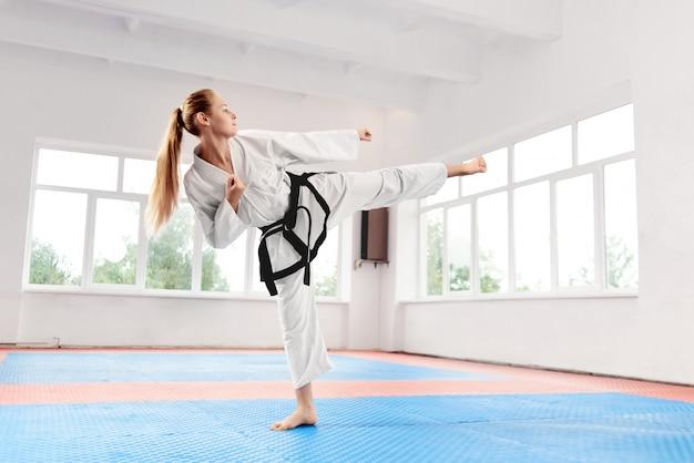 Lutador feminino realizando chute com legr levantada, melhorando a técnica de luta.