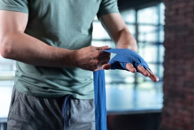 Lutador forte. lutador de músculos fortes vestindo shorts cinza e camisa cáqui enrolando as mãos em faixas de pulso