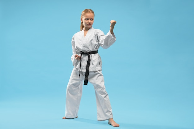 Lutador no quimono, olhando de lado e lutando no estúdio