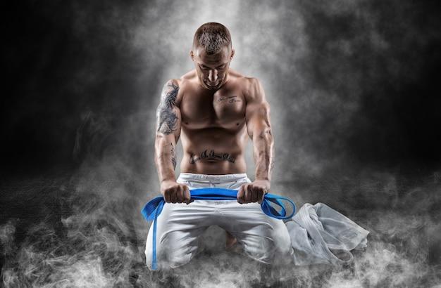Lutador profissional senta-se na fumaça com uma faixa azul nas mãos e ora. o conceito de artes marciais mistas, caratê, sambo, judô, jiu-jitsu. mídia mista