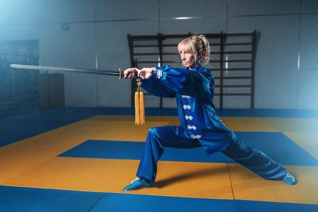 Lutadora de wushu feminina com espada em ação, artes marciais. mulher em pano azul posa com lâmina