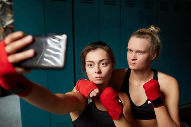 Lutadoras do sexo feminino tomando selfie no clube
