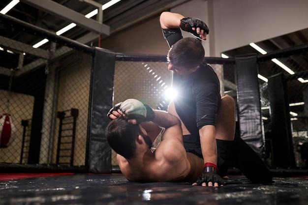 Lutadores de boxeadores musculosos de mma lutam em lutas sem regras nos octógonos do ringue. artistas de artes marciais mistas durante a luta. conceito de esporte e boxe