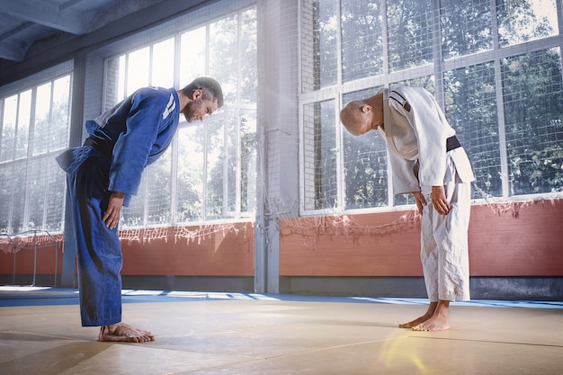 Lutadores de judô cumprimentando um ao outro em um arco antes de praticar artes marciais em um clube de luta