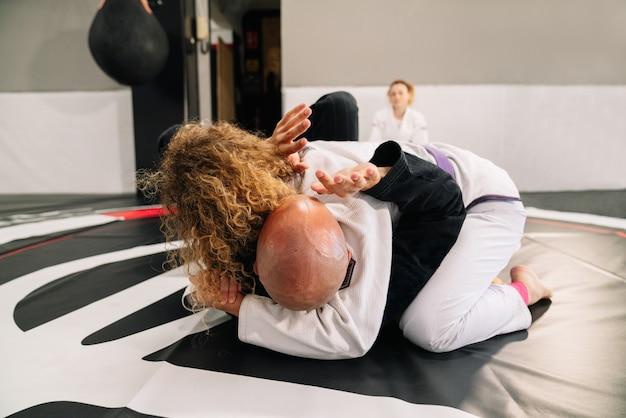 Lutadores de judô de artes marciais praticando novas técnicas em um tapete de ginástica