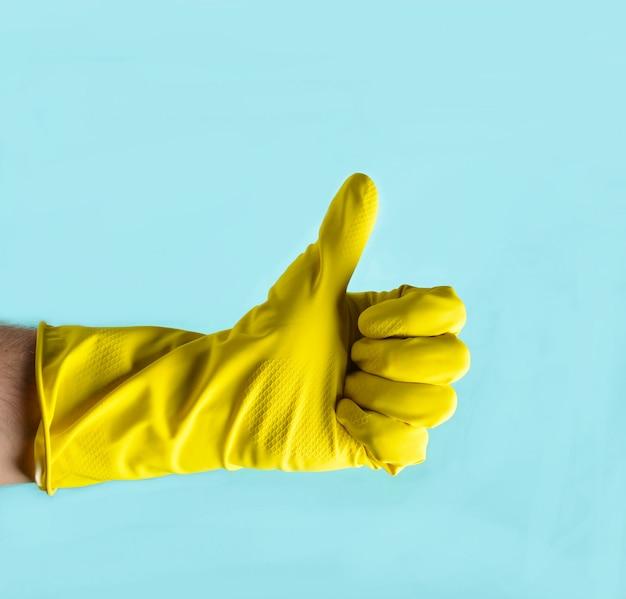 Luva amarela para limpeza no braço dos homens mostra os polegares