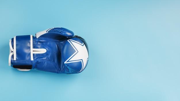 Luva de boxe azul em um fundo azul, espaço livre