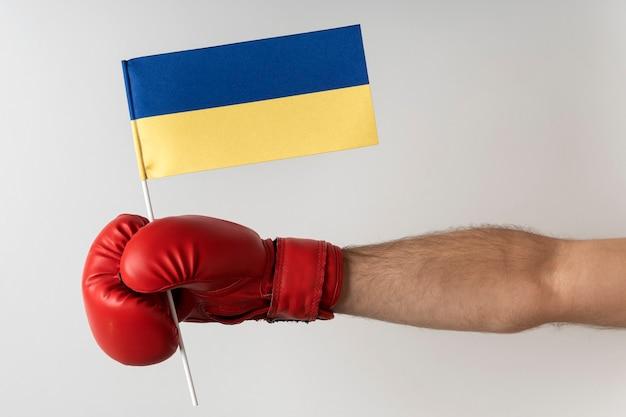 Luva de boxe com bandeira ucraniana. boxer segura bandeira da ucrânia. superfície branca.