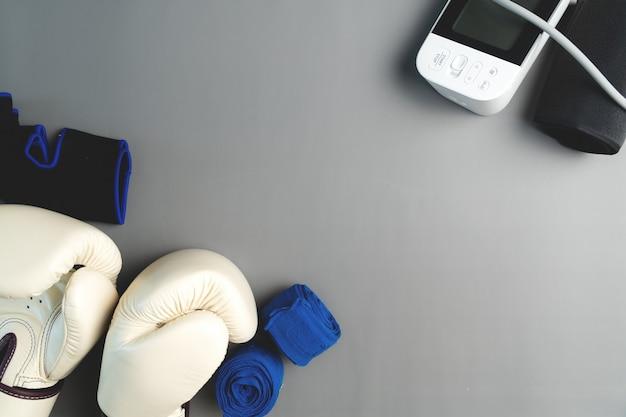 Luva de boxe, esfigmomanômetro, equipamento de fitness em fundo cinza com espaço de cópia
