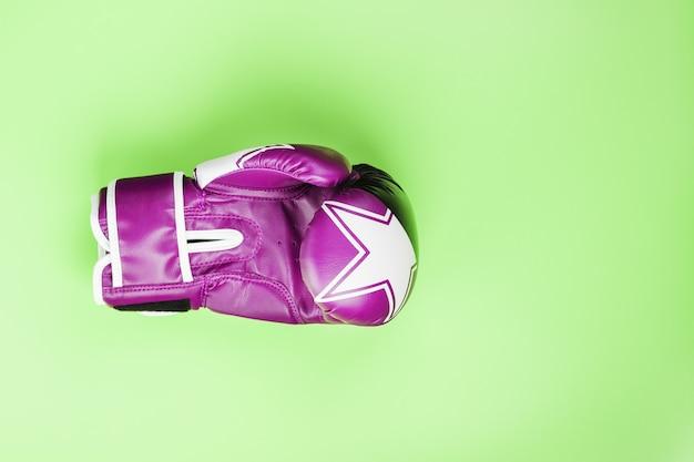 Luva de boxe rosa sobre fundo verde