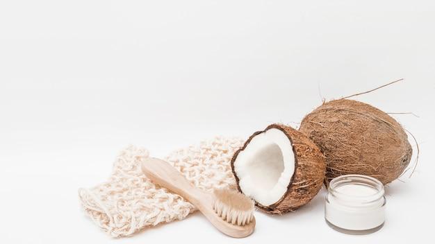 Luva macia; escova; coco e creme hidratante no fundo branco