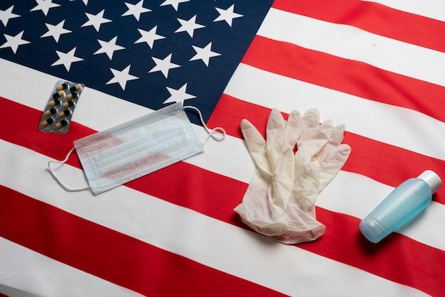Luvas anti-sépticas e máscara na bandeira americana como símbolo de quarentena e proteção contra vírus