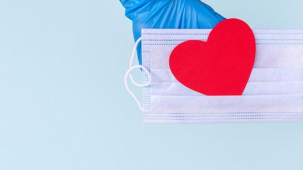 Luvas azuis segurando uma máscara médica com um coração vermelho de amor de papel