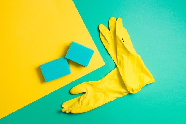 Luvas de borracha amarela e esponjas para lavar pratos em uma superfície verde e amarela