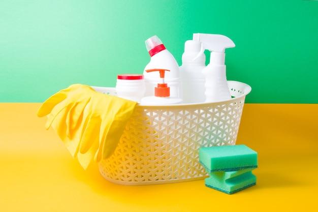 Luvas de borracha amarela, um pano amarelo para limpeza e diversas garrafas de plástico brancas com detergentes para a casa em um cesto sobre uma superfície amarela e verde