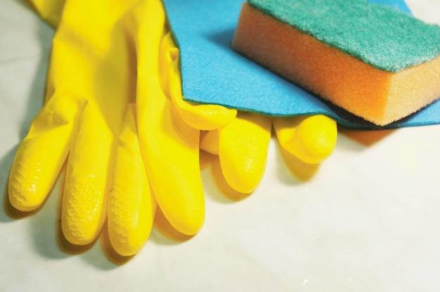 Luvas de borracha de proteção amarela, esponja e pano de prato