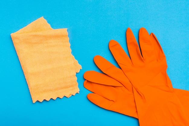 Luvas de borracha laranja e um pano de microfibra amarelo sobre um fundo azul