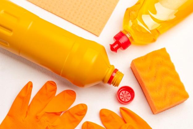 Luvas de borracha laranja. frasco de líquido laranja, esponja amarela e pano amarelo. limpando produtos. fundo branco. postura plana